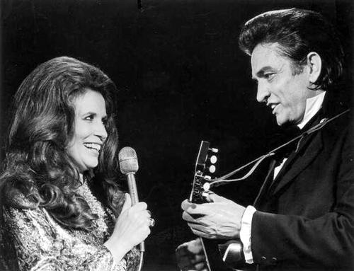 Married country singers Johnny Cash (1932 - 2003) and June Carter Cash (1929 - 2003) perform a duet on stage.  (Photo by Archive Photos/Getty Images)